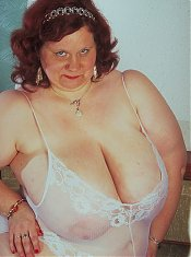 This chunky older babe with a massive set of knockers loosens her negligee to play with her bazooms